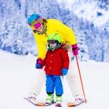 家庭在冬天山的滑雪和雪乐趣 免版税库存图片