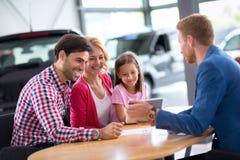 年轻家庭在售车行中 库存图片