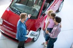年轻家庭在售车行交谊厅 图库摄影