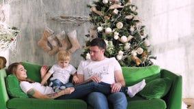 家庭在圣诞树附近聚集了 使用在长沙发 圣诞节内部 影视素材