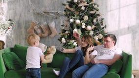 家庭在圣诞树附近聚集了 使用在长沙发 圣诞节内部 股票录像