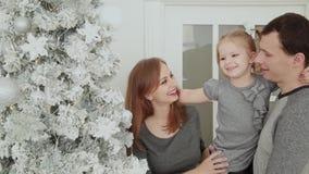 家庭在圣诞树,笑的谈和感人的玩具附近站立,当等待圣诞节时 影视素材