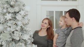 家庭在圣诞树,笑的谈和感人的玩具附近站立,当等待圣诞节时 股票视频