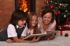 家庭在圣诞节时间的读书故事 库存图片