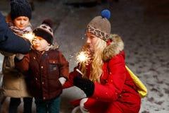 家庭在圣诞节的被点燃的闪烁发光物 免版税库存照片