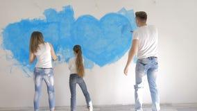 家庭在墙壁上的凹道心脏有蓝色油漆的 愉快的日概念 股票录像