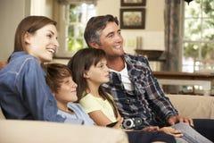家庭在家坐一起看电视的沙发 免版税库存照片