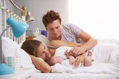家庭在拿着睡觉的新出生的小女儿的床上 库存图片