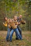 家庭在有赞许的秋天森林里 库存图片