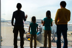 家庭在机场,旅行概念,父母剪影有孩子的在终端等待的飞行 免版税库存照片