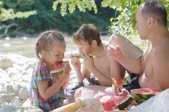 家庭在树荫下的吃新西瓜切片在海滩 免版税库存照片