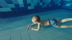 家庭在水池游泳 父亲教小儿子潜水到水池的深度在后的 股票视频
