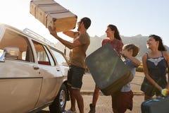 家庭在汽车行李架上的装货行李准备好旅行 免版税库存图片