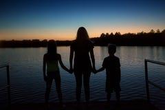 家庭在湖的剪影日落在度假 免版税库存图片