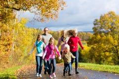 家庭在秋天森林里散步 免版税库存照片