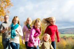 家庭在秋天森林里散步 库存图片