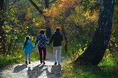 家庭在秋天森林里走 免版税库存图片
