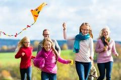 家庭在秋天森林飞行风筝的作为步行 免版税库存照片