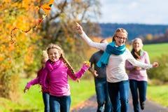 家庭在秋天森林飞行风筝的作为步行 免版税库存图片