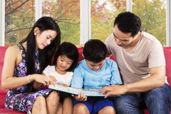 家庭在长沙发读了一本书 免版税库存照片