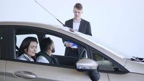 年轻家庭在陈列室、汽车购买和成功概念,开会里选择一辆新的汽车在汽车并且沟通与 股票录像