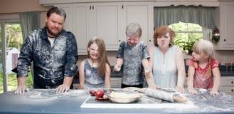 家庭在食物战斗以后的厨房里 免版税库存图片