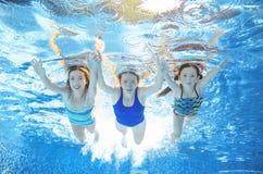 家庭在水池游泳在水,愉快的活跃母亲下,并且孩子有乐趣、健身和体育与孩子在度假 免版税库存图片