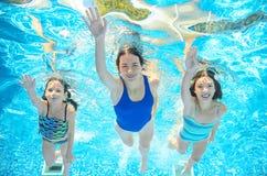 家庭在水池游泳在水,愉快的活跃母亲下,并且孩子有乐趣水中,孩子体育 免版税库存图片