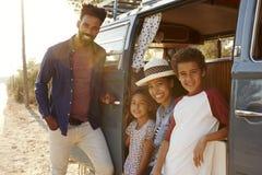 年轻家庭在他们的露营者货车的一次旅行做中止 免版税库存图片
