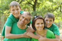 家庭在绿色森林里 库存照片