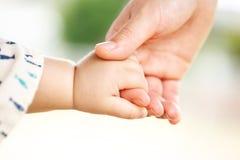 家庭场面、结合在一起使手的特写镜头父母和婴孩 免版税库存照片