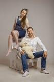 年轻家庭坐与Teddybear的一架梯子 免版税库存照片