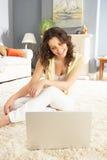 家庭坐使用妇女的膝上型计算机松弛&# 免版税库存照片