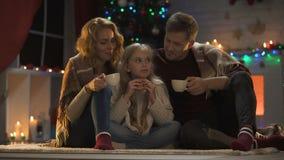 家庭坐喝热的茶、圣诞树和光的地板闪耀 股票录像