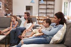家庭坐在开放学制休息室观看的电视的沙发 库存照片