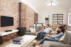 家庭坐在开放学制休息室观看的电视的沙发 库存图片