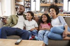 家庭坐在开放学制休息室观看的电视的沙发 免版税库存图片