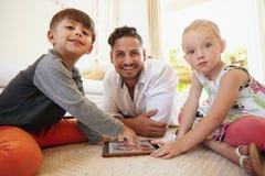 家庭坐地板使用数字式片剂 免版税库存图片
