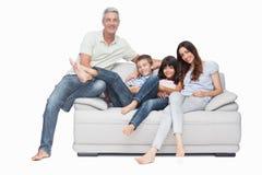 家庭坐微笑对照相机的沙发 免版税库存图片