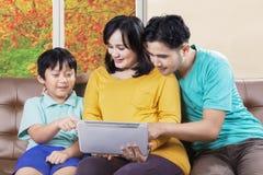家庭坐有数字式片剂的沙发 库存图片