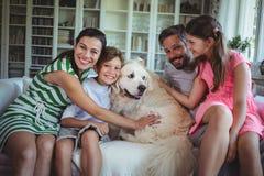 家庭坐有爱犬的沙发在客厅 免版税库存照片