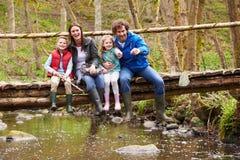 家庭坐桥梁渔在有网的池塘 库存图片