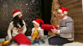 家庭坐毛皮卧具和使用与在圣诞老人帽子的枕头 股票视频