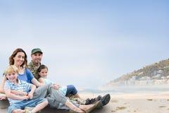 家庭坐沙子反对海岸线背景 免版税库存图片