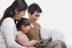家庭坐看膝上型计算机,演播室射击的沙发 库存照片