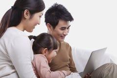 家庭坐看膝上型计算机,演播室射击的沙发 免版税库存图片