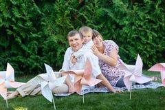 年轻家庭坐草在有玩具的一个公园 免版税库存图片