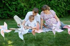 年轻家庭坐草在有玩具的一个公园 图库摄影
