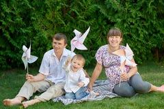年轻家庭坐草在有玩具的一个公园 库存照片