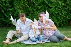 年轻家庭坐草在有玩具的一个公园 免版税图库摄影